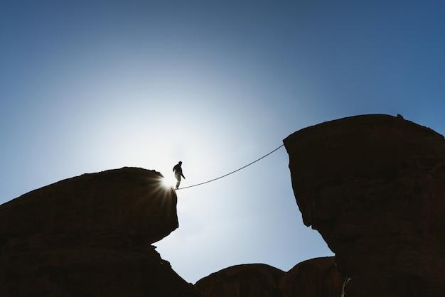 Concetto di sfida, rischio, concentrazione e coraggio. profili un equilibrio dell'uomo che cammina sulla corda sopra il precipizio Foto Premium