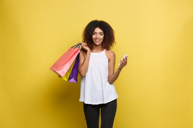 Concetto di shopping - close up ritratto di giovane bella donna attraente africana sorridente e gioiosa con shopping bag colorato. giallo pastello sfondo muro. copia spazio. Foto Gratuite
