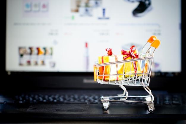 Concetto di shopping online, carrello, piccole scatole, computer portatile sulla scrivania Foto Premium
