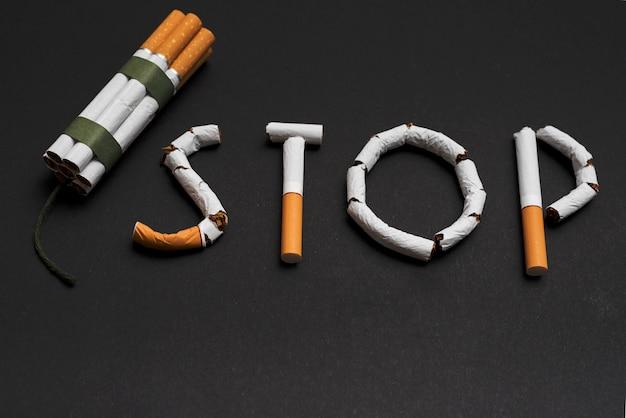Concetto di smettere di fumare con un mucchio di sigarette su sfondo nero Foto Gratuite