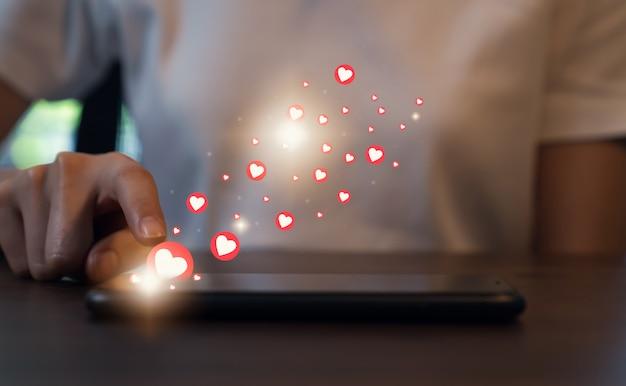 Concetto di social network. telefono della stampa della mano della donna e icona del cuore di manifestazione. Foto Premium