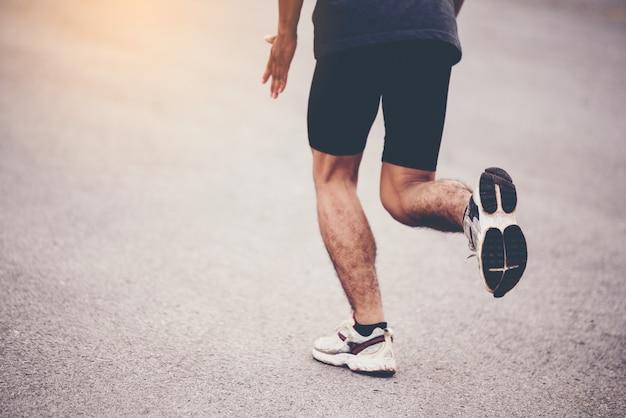 Concetto di sport, primo piano l'uomo con il corridore per strada Foto Gratuite