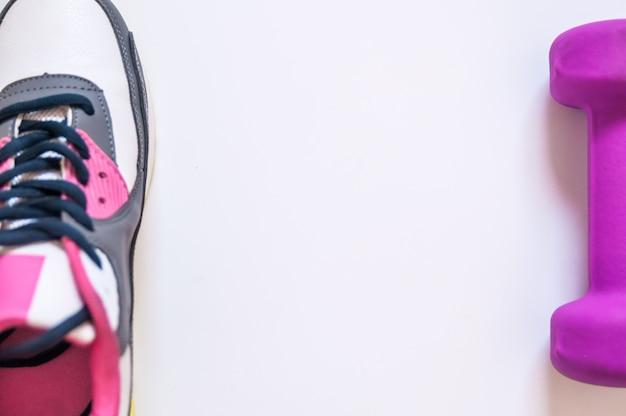 Concetto di sport, scarpe da ginnastica e manubri su sfondo