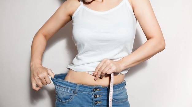 Concetto di stile di vita dieta donna e sanità per ridurre la pancia e modellare il muscolo dello stomaco sano. Foto Premium