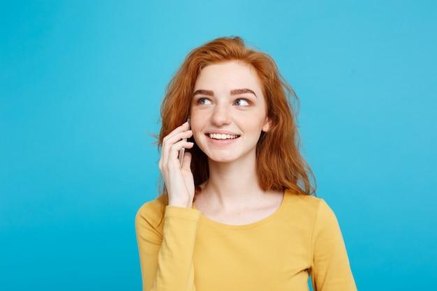 Concetto di stile di vita e tecnologia - ritratto di allegra felice ragazza di capelli rossi zenzero con gioiosa ed eccitante conversazione con l'amico dal telefono cellulare. isolato su sfondo blu pastello. copia spazio. Foto Premium