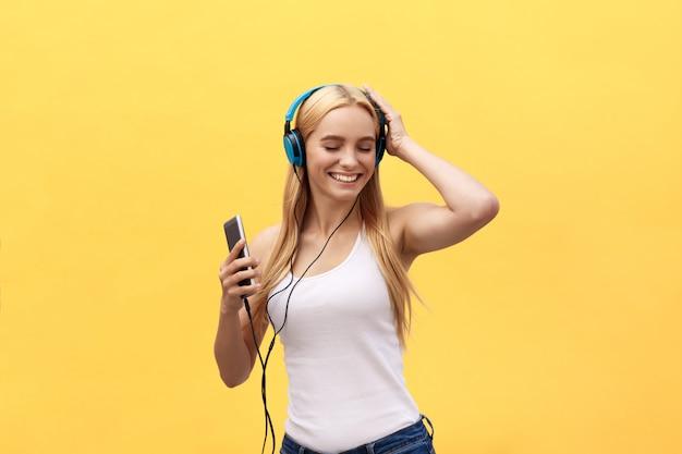 Concetto di stile di vita: ritratto di una donna gioiosa in t-shirt bianca e ascoltare musica Foto Premium