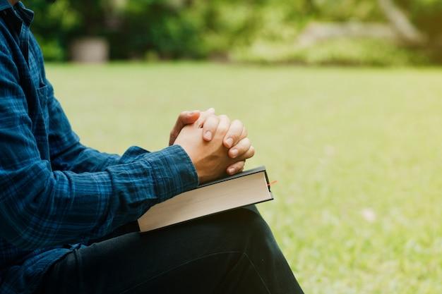 Concetto di studio della bibbia e dei cristiani. giovane uomo seduto e preghiera sullo spazio della bibbia Foto Premium