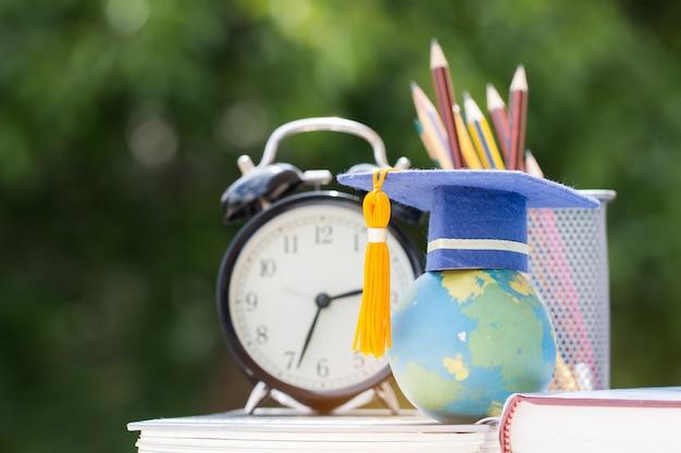 Concetto di studio di laurea o di educazione all'estero concetto: tappo di laurea sul libro di testo Foto Premium