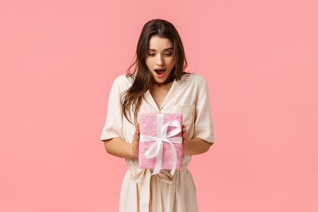 Concetto di stupore, celebrazione e vacanze. la ragazza sorpresa che tiene la scatola del presente, non si aspettava di ricevere il regalo, la bocca aperta ha affascinato lo sguardo ha toccato la scatola avvolta, fondo rosa Foto Premium