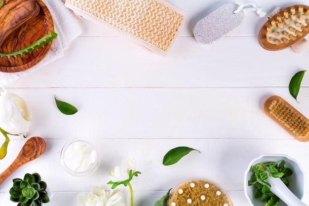 Concetto di trattamento termale con foglie verdi, prodotti cosmetici naturali e massaggio pennello su legno bianco Foto Premium