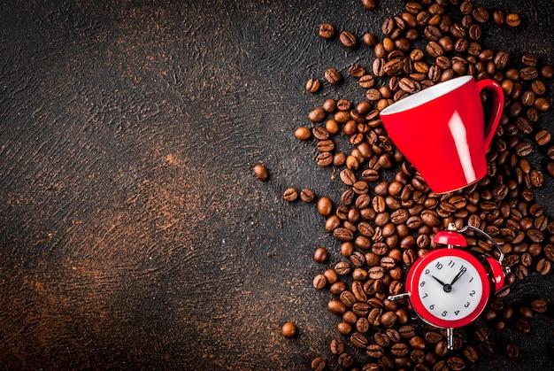 Concetto di un allegro, buon inizio di giornata, caffè mattutino. sfondo arrugginito scuro con chicchi di caffè, una sveglia e una tazza di caffè. vista dall'alto copia spazio Foto Premium