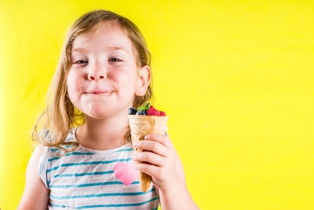 Concetto di vacanza di divertimento di estate, ragazza bionda sveglia del bambino che mangia le bacche dal cono gelato della cialda, fondo giallo luminoso Foto Premium
