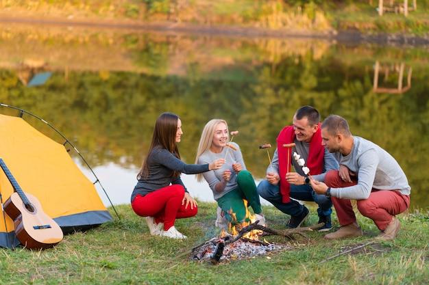 Concetto di viaggio, di turismo, di escursione, di picnic e della gente - gruppo di amici felici che friggono le salsiccie sul fuoco vicino al lago. Foto Premium