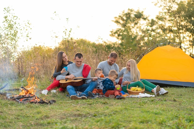 Concetto di viaggio, di turismo, di escursione, di picnic e della gente - gruppo di amici felici con la tenda e bevande che giocano chitarra al campeggio Foto Premium