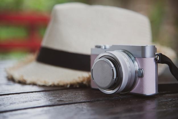 Concetto di viaggio di vista superiore con fotocamera e cappello sul tavolo Foto Gratuite