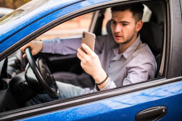 Concetto di viaggio, trasporto, viaggi, tecnologia e persone. uomo sorridente felice con lo smartphone che guida in automobile e che prende foto sul telefono Foto Gratuite