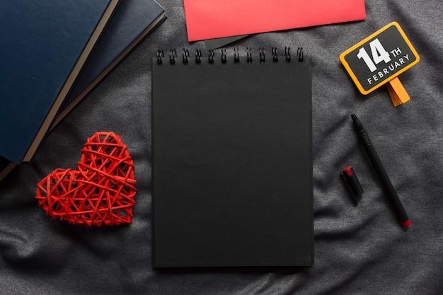 Concetto felice di san valentino, libro nero, cuore rosso e penna sul panno grigio Foto Premium