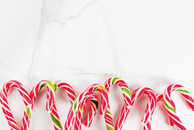 Concetto festivo di natale, un sacco di canna da zucchero candito dolci tradizionali di capodanno su un tavolo di marmo bianco. , vista dall'alto copyspace Foto Premium