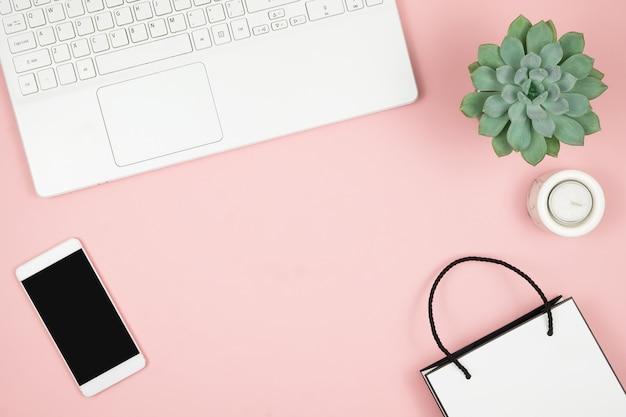 Concetto in linea di compera. le mani delle donne con il telefono e il computer portatile su superficie rosa. vista dall'alto, copia spazio. Foto Premium