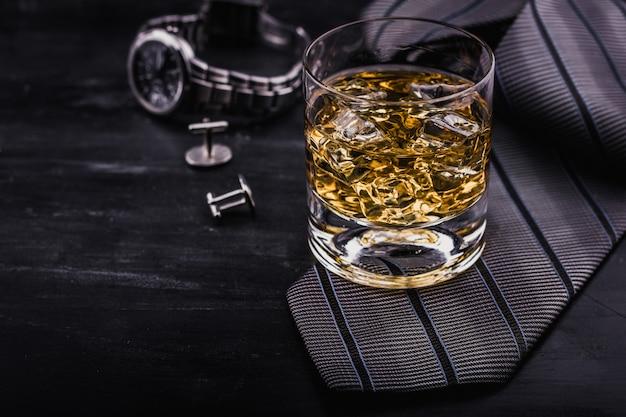 Concetto maschile per la festa del papà. cravatta, orologi, gemelli e un bicchiere di whisky con ghiaccio Foto Premium