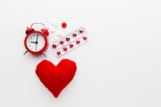 Concetto medico rosso e bianco con l'orologio e le pillole Foto Gratuite