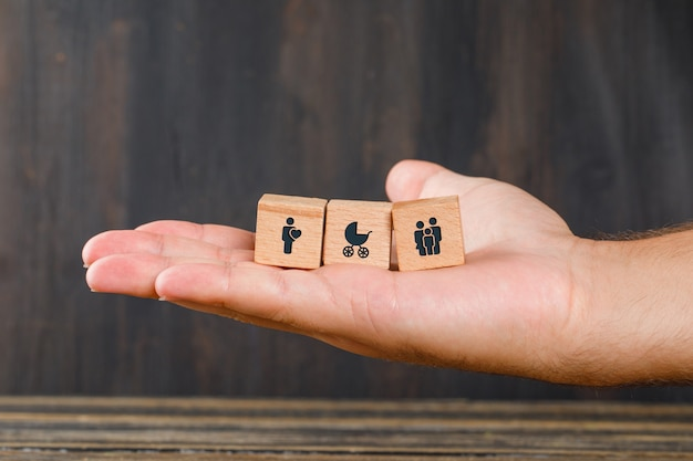 Concetto nucleo familiare sulla vista laterale della tavola di legno. mano che tiene i cubi di legno con le icone. Foto Gratuite