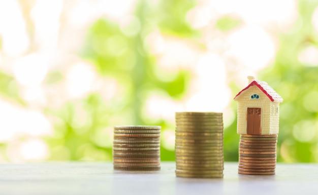 Concetto per scala di proprietà, casa e pila di monete per il risparmio di acquistare una casa Foto Premium