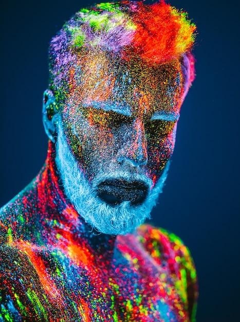 Concetto. ritratto di un uomo barbuto. l'uomo è dipinto in polvere ultravioletta. Foto Premium