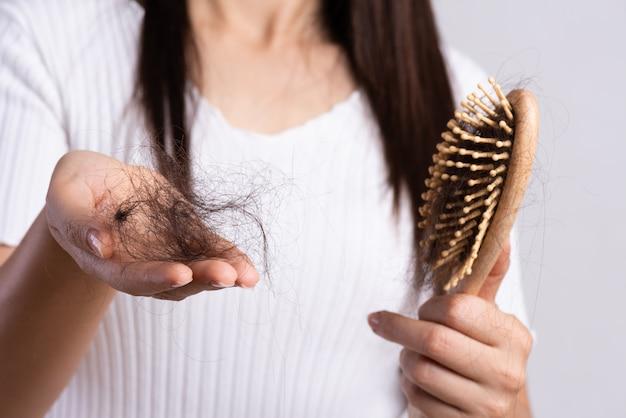 Concetto sano. la donna mostra la sua spazzola con i capelli danneggiati a perdita lunga Foto Premium