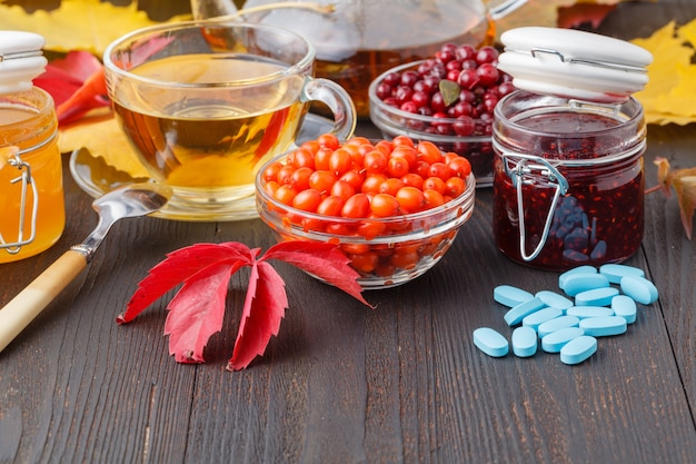 Concetto sano. tè della bacca di inverno con i mirtilli rossi, il miele e il timo in una tazza di vetro sulla tavola di legno. alternativo alla medicina tradizionale Foto Premium