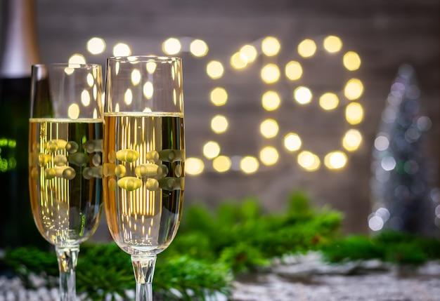 Concetto-vetro della decorazione del nuovo anno di champagne sul fondo vago del nuovo anno Foto Premium