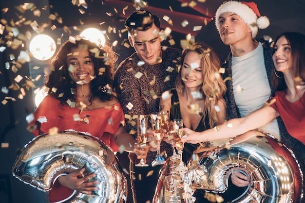 Concezione del nuovo anno. foto della compagnia di amici che hanno la festa con l'alcol Foto Premium
