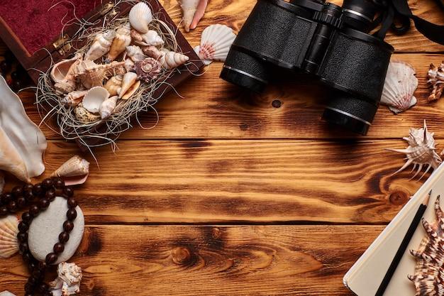 Conchiglie nella piccola scatola di legno aperta o scrigno sullo sfondo in legno circondato da altre conchiglie, pietre, con coroncina, vecchio binocolo, matita e quaderno di schizzi Foto Premium