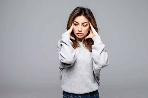 Condizione d'uso del maglione della bella giovane donna turbata, soffrendo di un'emicrania isolata sopra la parete grigia Foto Gratuite