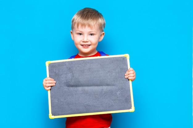Condizione della lavagna del gesso della tenuta del piccolo bambino Foto Premium