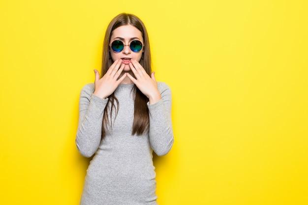 Condizione di grido emozionante della giovane donna isolata sopra la parete gialla Foto Gratuite