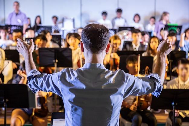 Conduttore di scuola maschile che dirige la sua banda studentesca per eseguire musica in un concerto scolastico Foto Premium