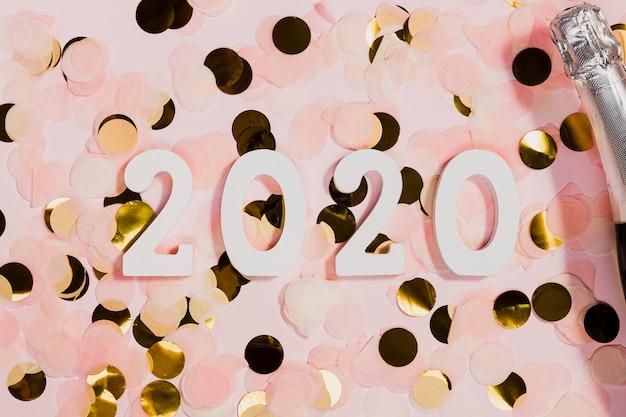 Confetti e bottiglia di champagne alla festa di capodanno Foto Gratuite