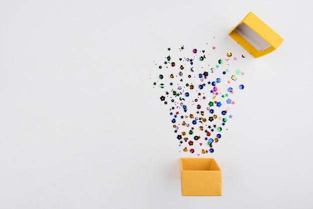 Confetti saltar fuori dalla scatola con copia-spazio Foto Gratuite