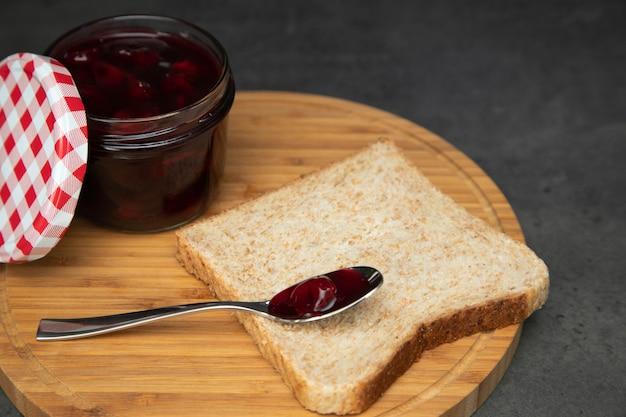 Confettura di ciliegie con bacche in un barattolo di vetro con un coperchio rosso e bianco aperto accanto. accanto a un toast integrale con un cucchiaino vuoto. Foto Premium