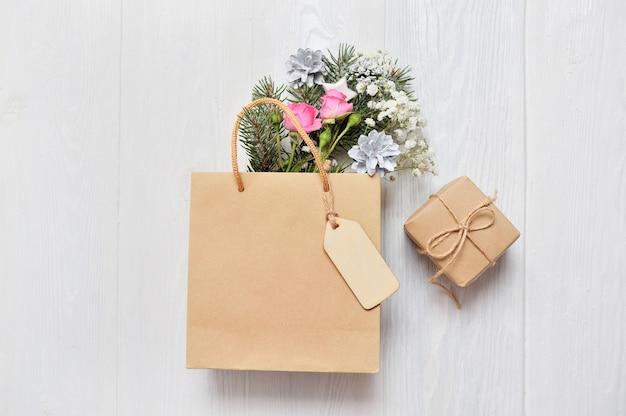 Confezione kraft con tag in legno e decorazioni natalizie rami di abete, rose rosa, coni Foto Premium