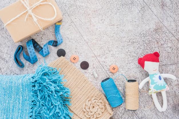 Confezione regalo avvolta; nastro di misurazione; pulsanti; rocchetto e bambola sullo sfondo texture Foto Gratuite
