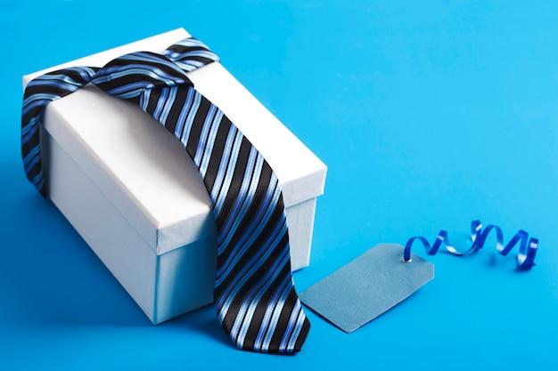 Confezione regalo con cravatta a righe blu. felice festa del papà idea, segno, simbolo. sfondo vacanza Foto Premium