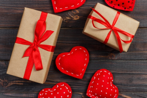 Confezione regalo con cuori di stoffa sul tavolo di legno nero Foto Premium
