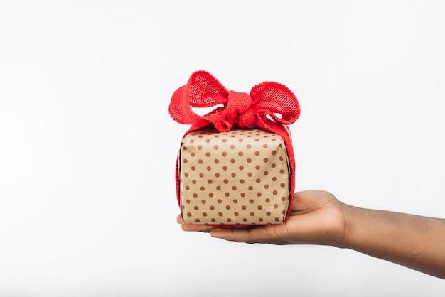 Confezione regalo con fiocco nelle mani di donna nera. Foto Premium