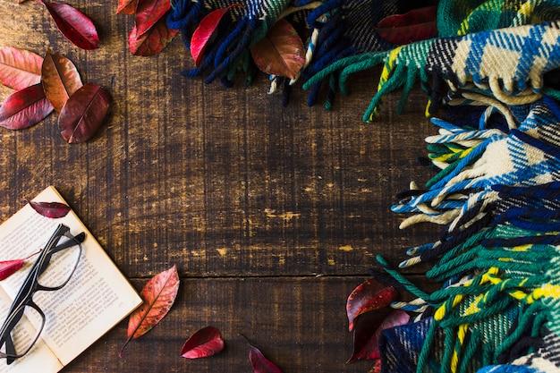 Confine dalla coperta e foglie vicino al libro e occhiali Foto Gratuite