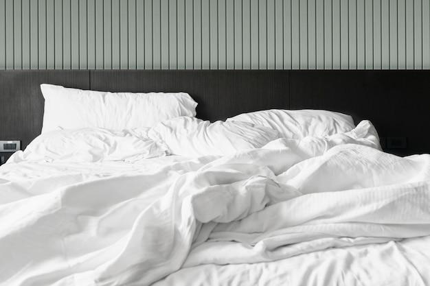 Confortevole camera da letto lenzuola bianche disordinate e piumone disordinato in camera da letto Foto Premium