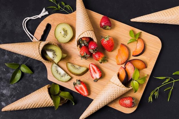 Coni gelati con frutta fresca sul bordo di legno Foto Gratuite