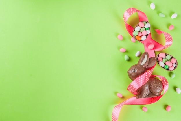 Coniglietto di pasqua al cioccolato, uova di caramella, uova di quaglia e nastro festivo Foto Premium
