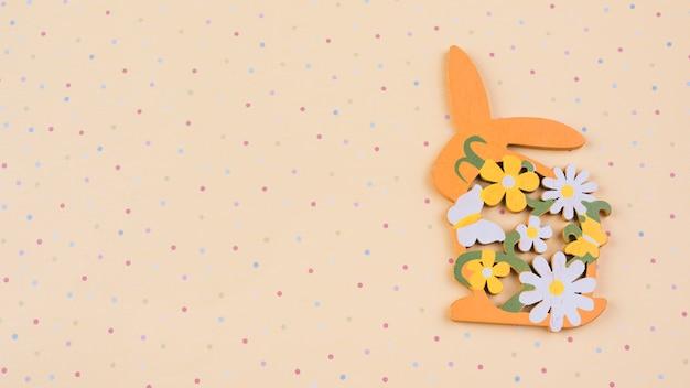 Coniglio in legno con fiori sul tavolo beige Foto Gratuite